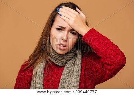 Close-up photo of unhealthy young caucasian woman touching her forehead, looking at camera, isolated on beige background