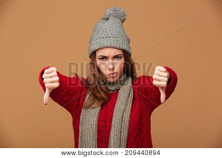 Close-up portrait of unhappy caucasian woman in winter clothes showing thumbs down gesture with two hands, looking at camera over beige background