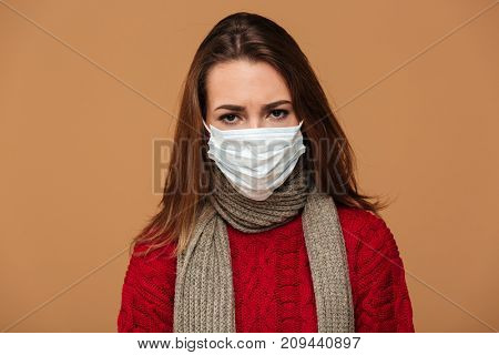 Young sick brunette woman in protective mask feeling bad over beige background