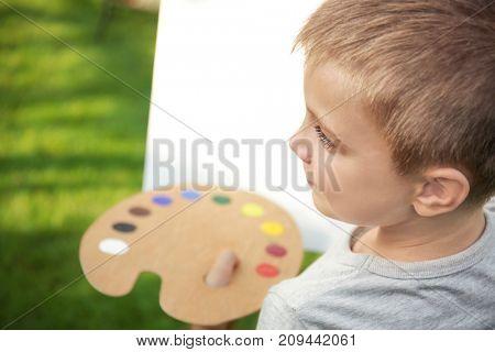 Cute little boy painting picture, closeup