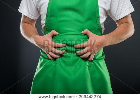Close-up Of Supermarket Employer Holding Belly Like Hurting