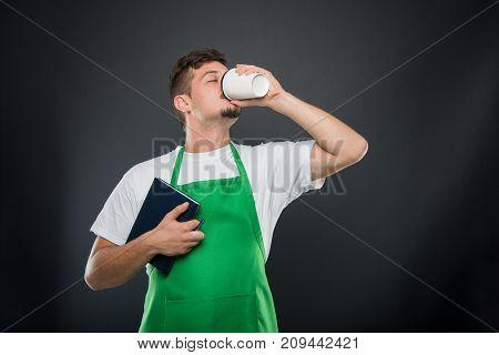 Portrait Of Supermarket Employer Holding Agenda Drinking Coffee