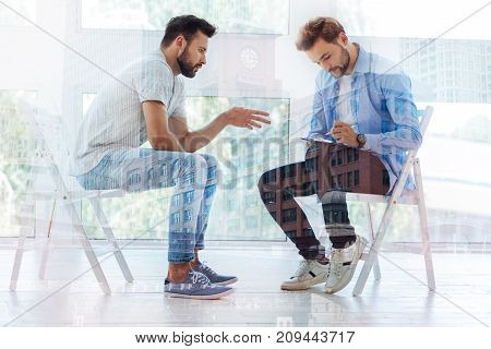 First appointment. Sad patient telling psychiatrist about his problems while psychiatrist writing down important facts