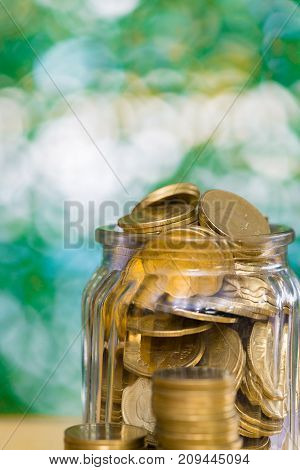 Gold Coin Money In The Glass Jar On Table In Garden With Green Background, For Saving Banking Financ