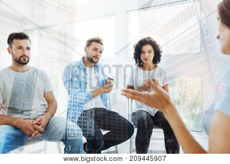 Looking for help. Group of friends listening to psychologist while being concentrated