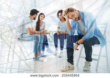 Discussing problems. Group of best friends talking with psychologist while their friend touching his head and being indifferent
