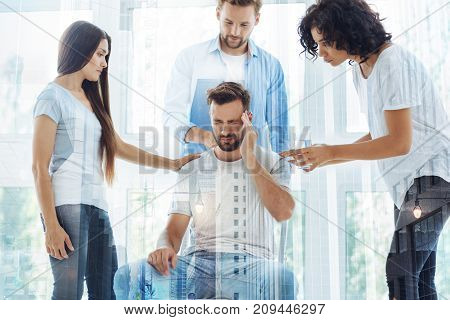 Totally worn out. Waist up of nervous man sitting on the chair and touching his head while his friends supporting him and expressing concern
