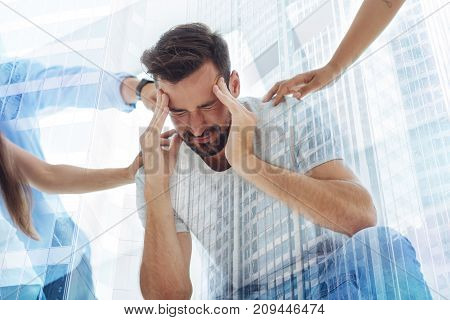 Being nervous. Close up of young bearded man feeling upset while keeping his eyes closed and expressing confusion