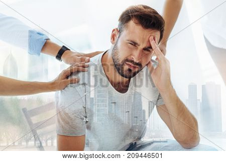Unsuccessful experience. Close up of nervous bearded man touching his face and looking at you while his friends supporting him