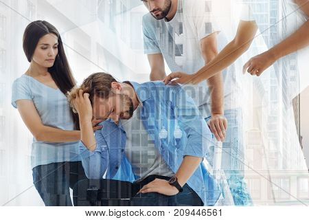 Bad news. Waist up of disappointed bearded man touching his hair while his friends helping him morally