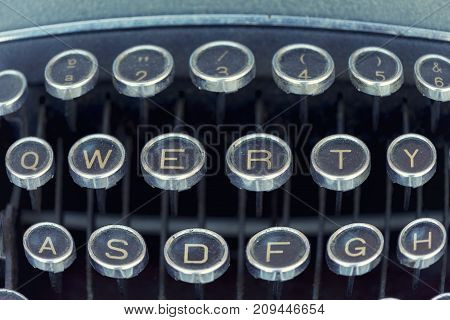 Close-up horizontal shot of a dusty obsolete typewriter with qwerty keyboard. poster