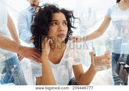Feeling dissatisfied. Close up of young woman with curly hair holding a glass of water in psychologists office while her friends giving moral support