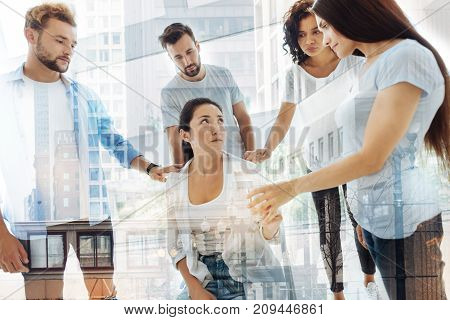 Supporting and understanding. Waist up of stressed woman sitting on the chair while her friends and psychologist calming her down