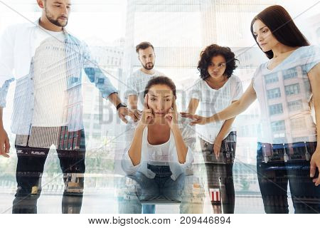 Hard life. Young nervous woman keeping fingers on temples while sitting in psychologists office and being supported by friends