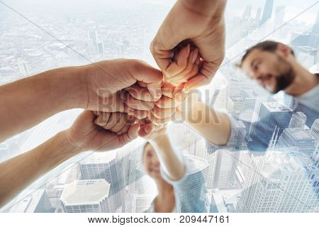 Professional workers. Close up of successful colleagues keeping fists together while standing in circle and expressing delight