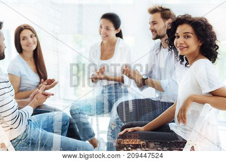 Maintaining moral health. Smiling pleasant friends sitting in circle while doing psychological exercises and expressing interest