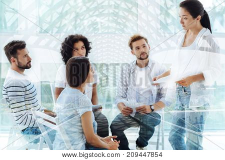 Constructive discussion. Young experienced psychologist standing in front of clients and giving pieces of advice while holding papers with information