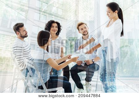 Analyzing moral world. Pleasant woman giving results of psychological tests to clients while standing in front of them and expressing concern