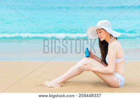 Attractive Happy Woman Using Sun Protection Oil