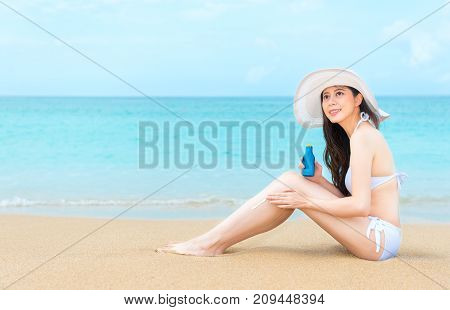 Young Female Model Sitting On Beach Daydreaming