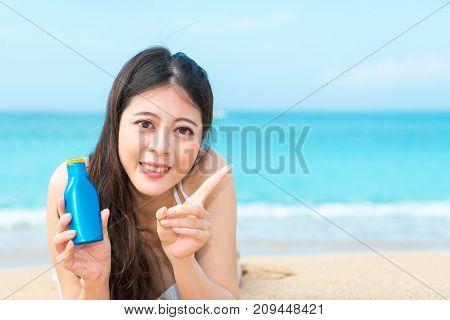 Attractive Elegant Girl Showing Sunscreen Bottle