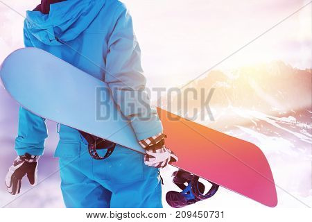 Ski concept with close up photo of snowboarder with snowboard in hands standing on background of big mountain