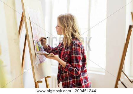 art school, creativity and people concept - student girl or artist with easel, palette and paint brush painting still life picture at studio