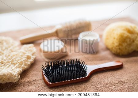 bodycare, beauty and spa concept - hair brush, body cream, sponge and soap bar on bath towel