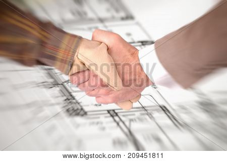 Worker and a businessman shaking hands over house renovation plans house renovation contract deal and plans