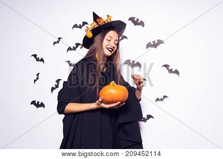 Halloween Witch with a Pumpkin and bats on a white background. Beautiful young woman in witches hat and costume holding pumpkin. Wide Halloween party art design