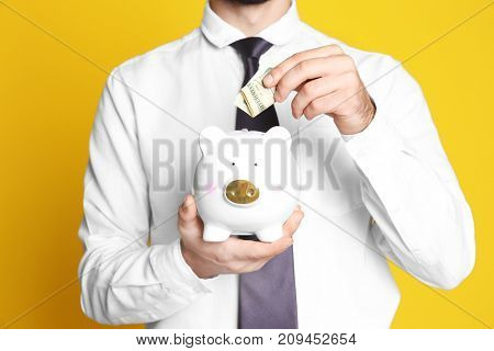 Young man putting banknote into piggy bank on color background