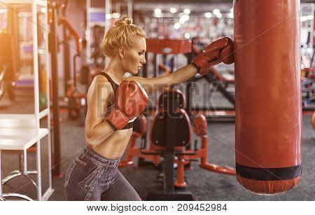 Female boxer in gloves training in gym