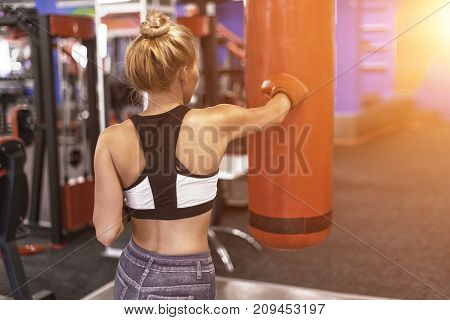 Attractive Female Punching A Bag With Boxing Gloves In Gym. Back View