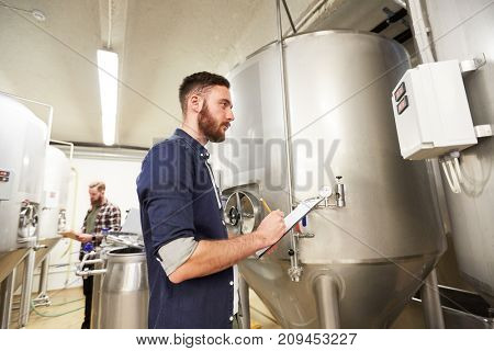 manufacture, business and people concept - men with clipboard working at craft brewery or non-alcoholic beer production plant