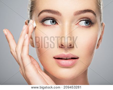 Beautiful young woman gets cream near eyes. Skin care concept. Stunning caucasian woman with perfect health clean skin. Portrait of an Attractive girl  with blue eyes, closeup.