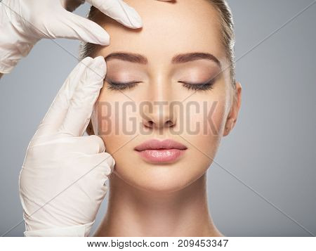 skin check before plastic surgery. Beautician touching woman face.