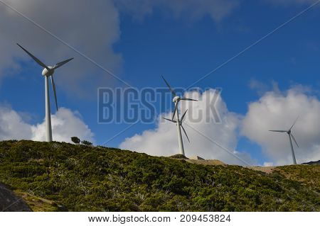 Several wind turbines with gray clouds in the mountains of the island of Crete