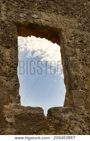 Blue sky with a white cloud seen through a window of a ruined wall