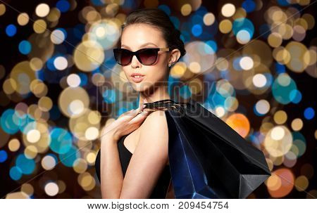 sale, fashion, people and luxury concept - happy beautiful young woman in black sunglasses with shopping bags over holidays lights background