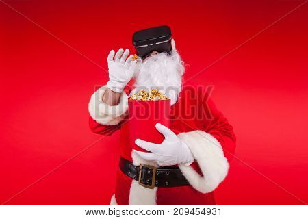 Santa Claus wearing virtual reality goggles and a red bucket with popcorn, on a red background. Christmas.