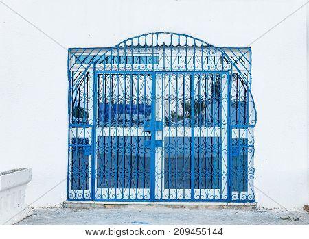 detail of building and blue decorative metal railing window in Monastir