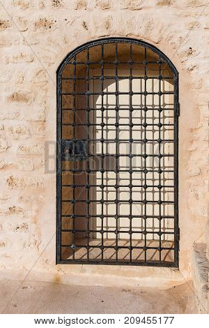 Metal grille in front of the gates set in a sandstone wall of the fort in Monastir. Metal grille. Tunisia.