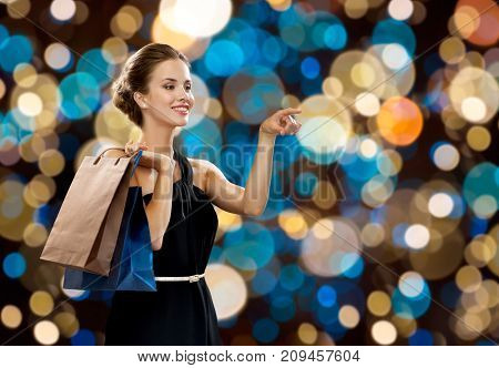 sale, fashion, people and luxury concept - happy beautiful young woman in black dress with shopping bags over holidays lights background