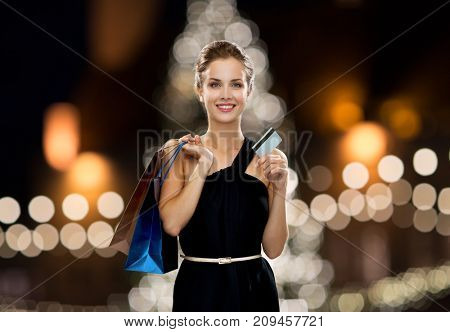 people, luxury and sale concept - beautiful woman with credit card and shopping bags over christmas tree lights background
