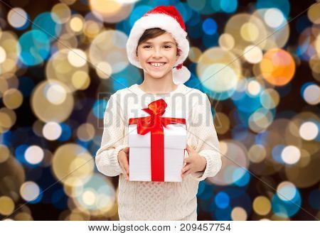 holidays, christmas, childhood and people concept - smiling happy boy in santa hat with gift box over lights background