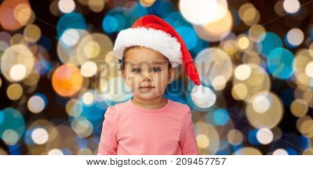 christmas, holidays and people concept - little baby girl in santa hat over lights background