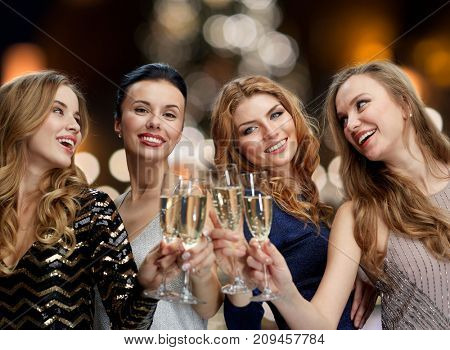holidays, celebration and people concept - happy women clinking non alcoholic champagne glasses at new year party over christmas tree lights background