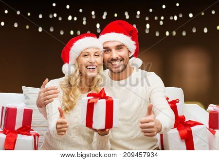 christmas, holidays and people concept - happy couple in santa hats with gift boxes sitting on sofa and showing thumbs up over garland lights background