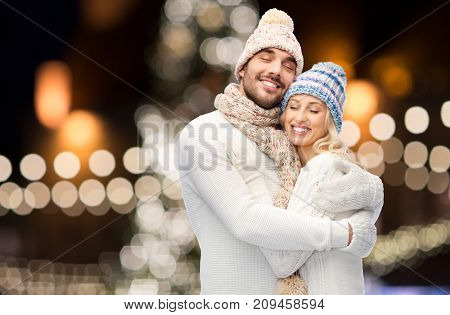 winter, holidays, christmas and people concept - happy couple in hats and scarf hugging over night lights background