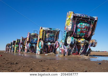 December 21 2015 Amarillo Texas USA: Cadillac Ranch is a roadside public art installation of old car wrecks and a popular landmark on historic Route 66. Tourists are spraying the wrecks with paint.